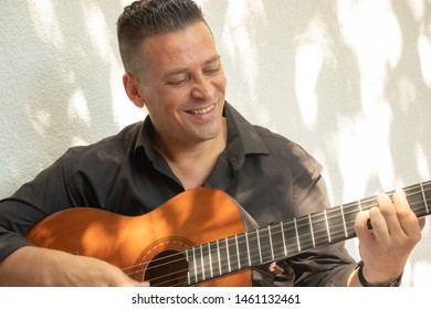 A handsome Spanish man, musician playing guitar and smiling because  he is happy.