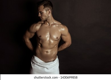 Handsome sport sexy stripped guy portrait with white towel on isolated black background