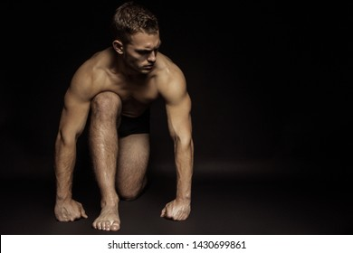 Handsome sport sexy stripped guy portrait on isolated black background