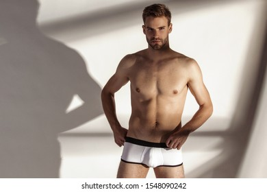 Handsome sport sexy stripped guy portrait with white underwear on isolated white background and shadows