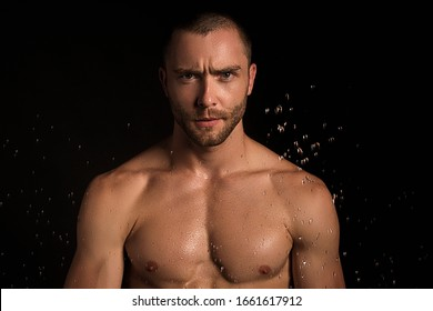 Handsome sport sexy stripped guy portrait for cosmetics and fitness drops on isolated black background