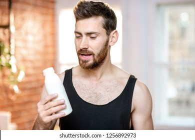Handsome sports man in black t-shirt with milk bottle at home