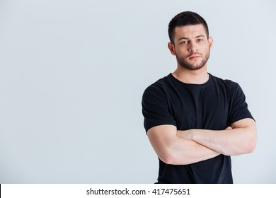 Handsome sports man standing with arms folded isolated on a white background