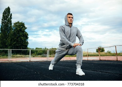 Handsome sportsman doing exercises for legs, lunges, dressed in sportswear, outdoors