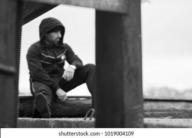 Handsome sportsman is resting on a gateway block during a brake in outdoor running workout. Face is out of focus like a concept of relax.
