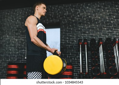 Handsome sportsman with sandbag on shoulders while exercises in the gym. Attractive athletic male doing hard workout with weight training with copy space for your text or advertising. Copy space