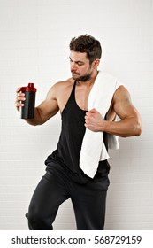 Handsome sportsman standing with towel holding a bottle over white background.