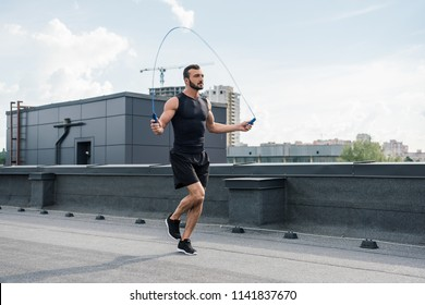 handsome sportsman training with jumping rope on roof