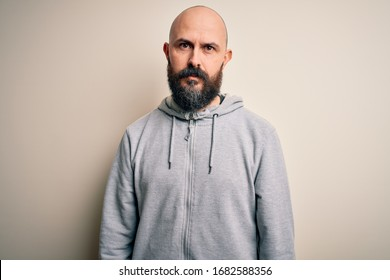 Handsome sporty bald man with beard wearing sweatshirt standing over pink background with serious expression on face. Simple and natural looking at the camera.
