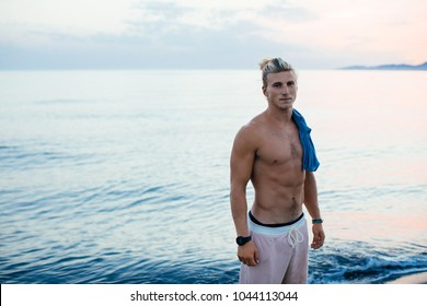 Handsome sporty Caucasian man standing by the sea and looking at camera.