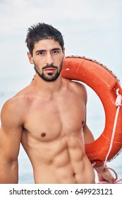 Handsome sporty lifeguard stands with lifebuoy