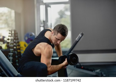 Handsome sporty man flexing muscles with barbell in dark gym. Sport concept. Atheletic muscular guy wearing sports pants and black jersey, doing exercise while sitting in dark gym. Concept of sport.