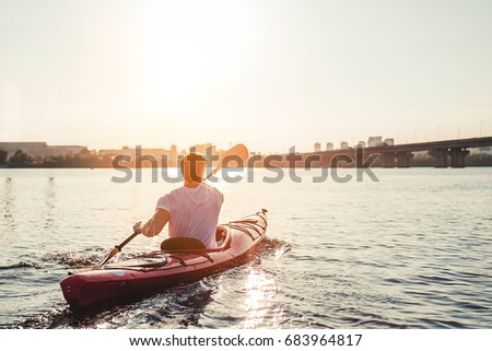 Handsome sporty man is kayaking on sunset on river. Canoeing alone.