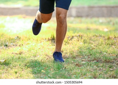 Handsome sporty man running in park