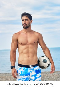 Handsome sporty man stands on the beach with football ball