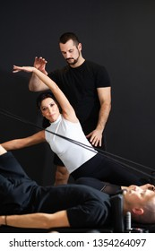 Handsome and sporty Pilates trainer instructing  beautiful young women at the gym,using Tower reformer,personal coaching concept