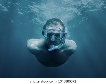Handsome sporty young man with snorkel and mask swimming underwater, looking at camera.