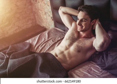 Handsome sporty young man in underwear is lying on bed under the blanket