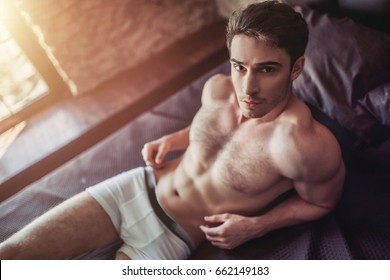 Handsome sporty young man in underwear is lying on bed