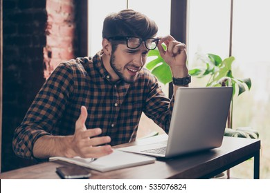 Handsome stressed  young man in glasses using  laptop