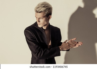 Handsome stripped blonde male model wearing black suit  on white isolated font background