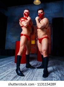 handsome striptease dancers dressed  in red stage costumes,  in the interior