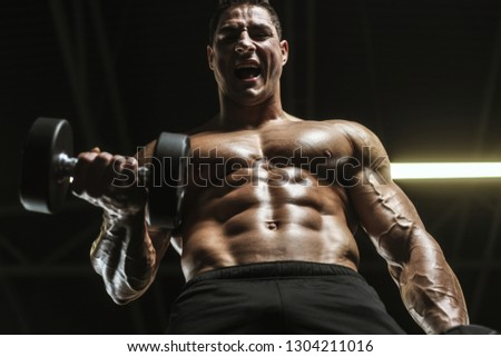Handsome Strong Athletic Men Pumping Muscles Stock Photo
