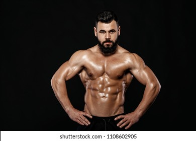 Handsome strong bodybuilder posing in studio isolated on black background