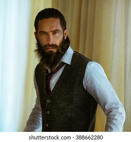 Handsome strong, brutal bearded man posing in suit