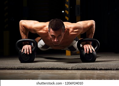 Handsome strong brutal man doing plank on kettlebells, push-up on weights on dark sport club background. Training in light gym on art shadow