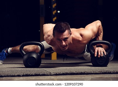 Handsome strong brutal man doing plank on kettlebells, push-up on weights on dark sport club background. Training in light gym on art shadow. Toned portrait