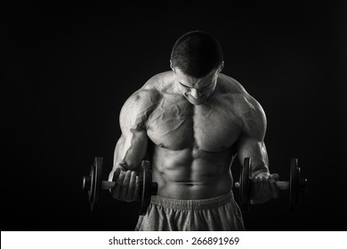 Handsome strong man with beautiful body in sport wear with dumbbell in hand isolated ob black background