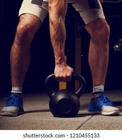 Handsome strong man holding one muscle arm the kettlebell on dark sport club background in fashion sneakers. Training in light gym. Toned vintage closeup portrait