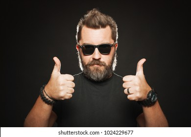 A handsome, strong man with a stylish hairstyle and beard shows two thumbs up in the Studio on a black background. With copy space for your text.