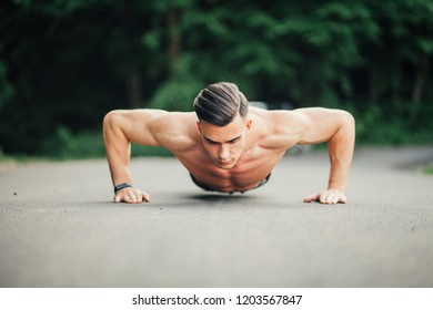 Handsome strong sporty male doing push up exercises outdoor