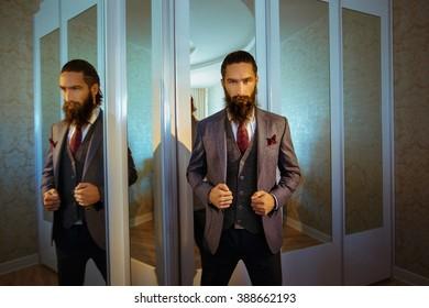 Handsome strong stylish bearded groom posing near mirror