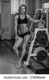 Handsome and strong woman with beautiful body doing exercises in gym.
