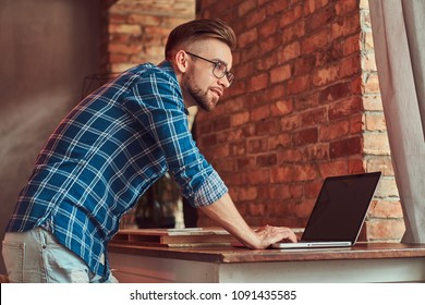 Handsome student in a flannel shirt working on a laptop computer in a room with a loft interior.