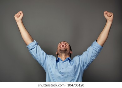 Handsome student with raised arms screaming