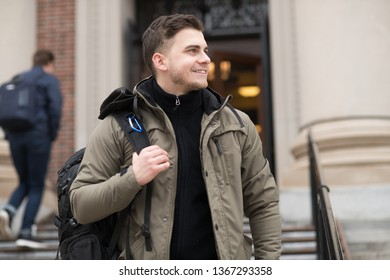 Handsome student walking in college campus with a backpack to the class