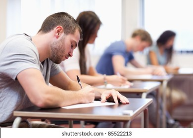 Handsome student writing an assignment in a classroom