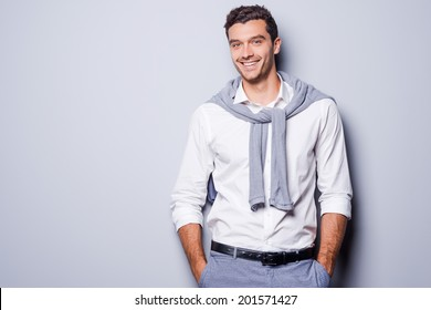 Handsome in style. Cheerful young man in smart casual wear looking at camera and holding hands in pockets while standing against grey background