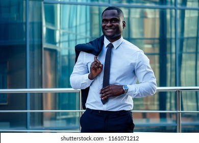 handsome and stylish African American model man in a fashionable black jacket and a white shirt with a collar with a elegant tie posing background of Manhattan glass offices cityscape