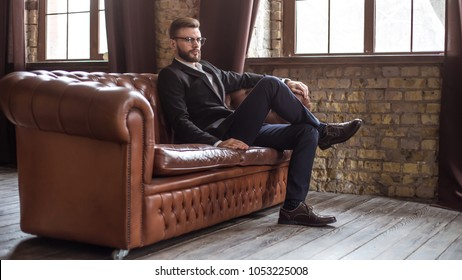 Handsome stylish confident bearded businessman in a smart suit and glasses sitting on a sofa in the office.