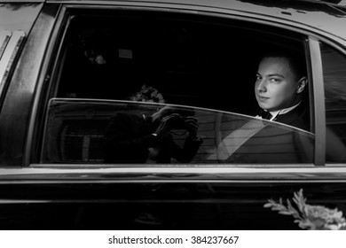 Handsome stylish groom with bouquet in the wedding car