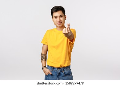 Handsome and stylish hipster asian guy in yellow t-shirt, with tattoos, extend arm and showing korean heart love sign, smiling silly, express affection, adore girlfriend, standing white background