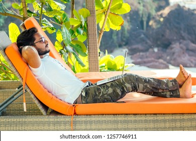 handsome stylish indian man summer vacation in tropical paradise relaxing on an orange deckchair against a background of green tropical trees.freelance remote work.fitness male relaxing on beach