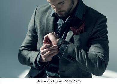 Handsome stylish man adjusting smartwatch on grey