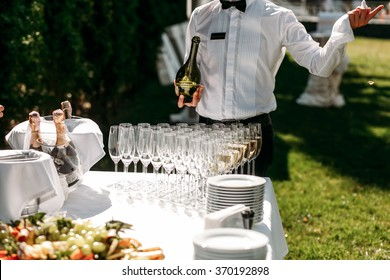 Handsome stylish man bartender opening  a bottle of champagne in the street in celebration of the wedding