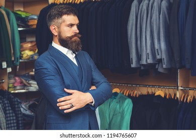 Handsome stylish man with beard in blue cloth jacket. Businessman in classic vest against row of suits in shop. It is in showroom, trying on clothes. Advertising photo, sale, discount, Black Friday.